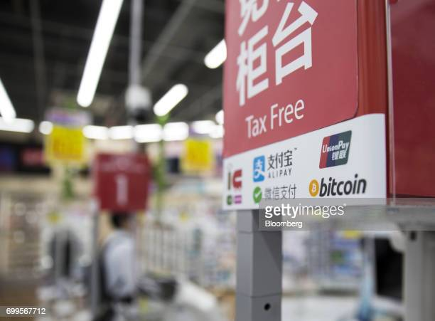 The logos of China UnionPay Co's UnionPay card top right and Bitcoin bottom right are seen at the information desk inside the Bic Camera Akiba...