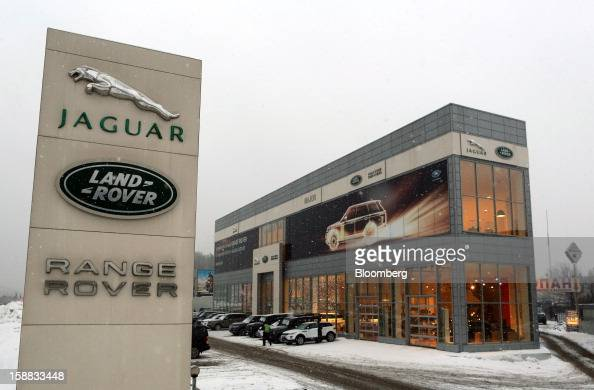 The logos of Jaguar Land Rover and Range Rover marques stand on display outside a Jaguar Land Rover auto dealership in Moscow Russia on Thursday Dec...