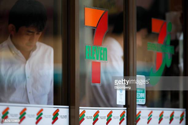 The logos of Seven I Holdings Co right and 7Eleven center are displayed at the entrance to a 7Eleven convenience store as a man exits in Tokyo Japan...
