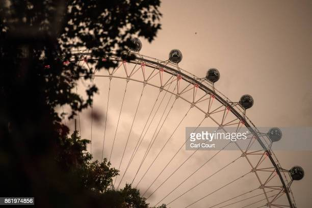 The London Eye is pictured during a reddish sky caused by remnants of Hurricane Ophelia dragging in dust from the Sahara Desert on October 16 2017 in...