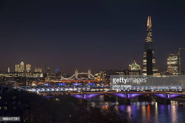 The London skyline at night including The Shard with Tower Bridge and Canary Wharf
