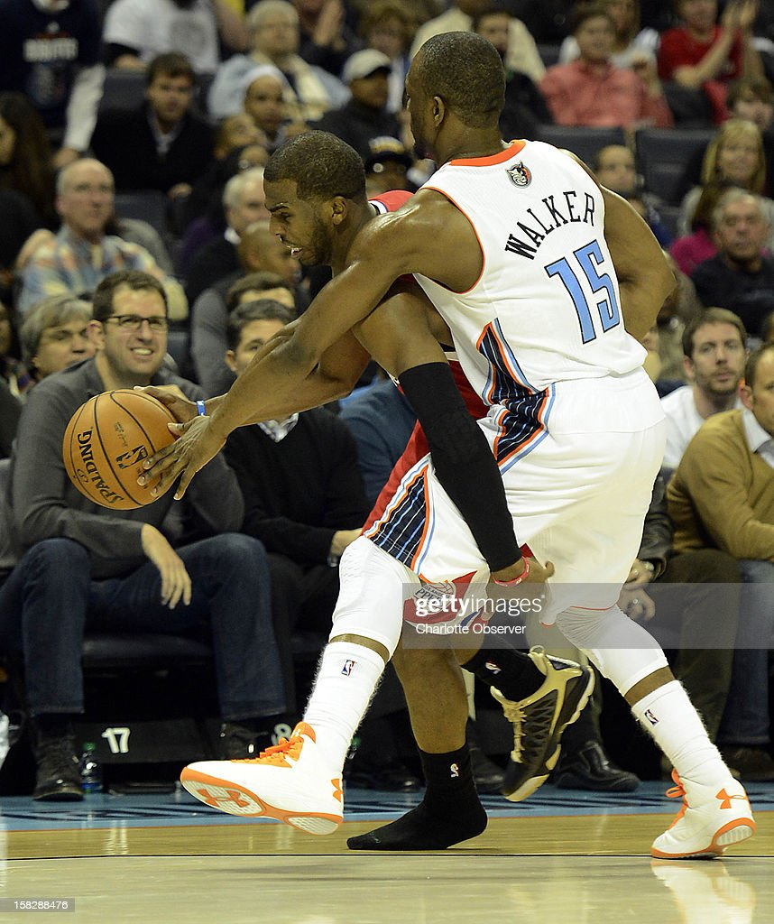 The Los Angeles Clippers' Chris Paul dribbles without his shoe as he is fouled by the Charlotte Bobcats' Kemba Walker (15) in the second half at Time Warner Cable Arena in Charlotte, North Carolina, on Wednesday, December 12, 2012. The Clippers won, 100-94.