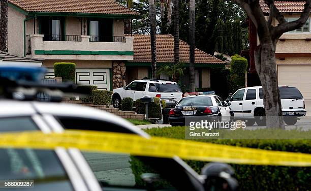 The Los Angeles County Sheriffs department investigates the scene at a stucco house with green trim where a 65yearold woman was shot and killed in...