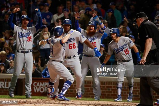 The Los Angeles Dodgers celebrate a grand slam by Enrique Hernandez in the third inning against the Chicago Cubs in Game 5 of the National League...