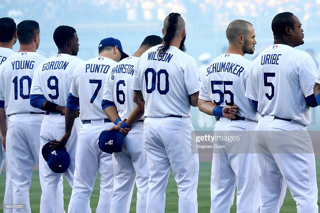 The Los Angeles Dodgers stand on the third base line during the national anthem before taking on the Atlanta Braves in Game Three of the National...