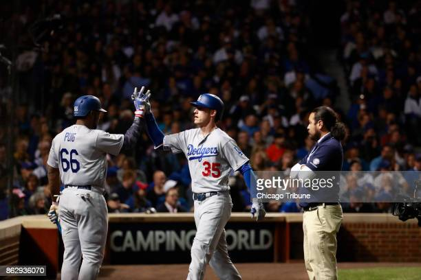 The Los Angeles Dodgers' Yasiel Puig highfives teammate Cody Bellinger after his thirdinning solo home run against the Chicago Cubs during Game 4 of...