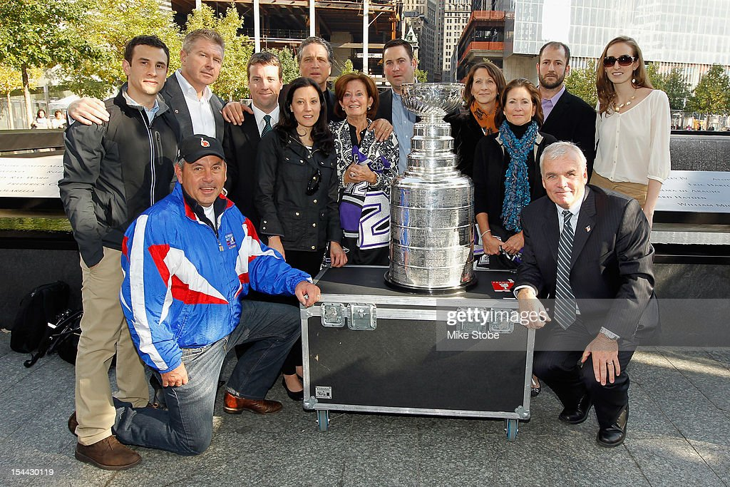 The Los Angeles Kings brought the Stanley Cup to Ground Zero in New York in conjunction with the National Hockey League, the Hockey Hall of Fame and the New York Police Department to pay tribute to former club scouts Garnet 'Ace' Bailey and Mark Bavis - pictured here are (L-R back row) Justin Lauri, Michael Futa, Steve Greeley, Dean Lombardi, Todd Bailey, Barbara Pothier, Katherine Bailey, Mark Yannetti, and Meagan Smith (L-R front row) Paul Sylvester, Colleen Bavis, Kathy Bavis Sylvester, Katherine Bailey and Mike O'Connell at the reflecting pools in lower Manhattan at the World Trade Center site on October 14, 2012 in New York City