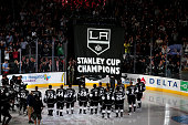 The Los Angeles Kings stands on the ice as the Stanley Cup Championship banner is unfurled during ceremonies before the game with the San Jose Sharks...
