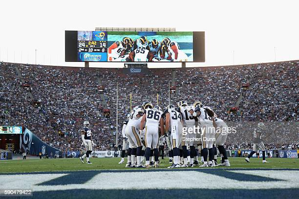 The Los Angeles Rams offense huddles with the video scoreboard in the background against the Dallas Cowboys at the Los Angeles Coliseum during...