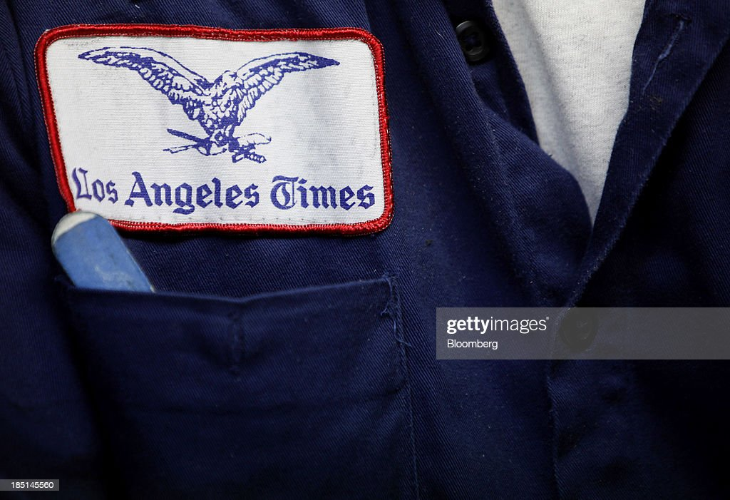 The Los Angeles Times newspaper logo is seen on a press operator's shirt at the Olympic Press facility in Los Angeles, California, U.S, on Wednesday, Oct. 16, 2013. Congress ended the 16-day government shutdown, raising the U.S. debt limit after the leaders of the Senate reached a bipartisan agreement to end the nation's fiscal impasse. Photographer: Patrick T. Fallon/Bloomberg via Getty Images