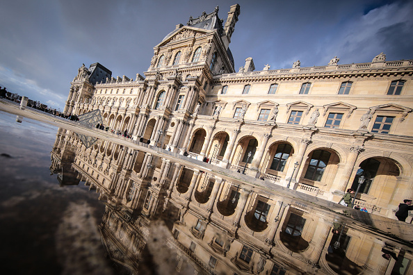 The Louvre Palace reflecting into a water puddle on February 7 2016 in the 1st quarter of Paris France