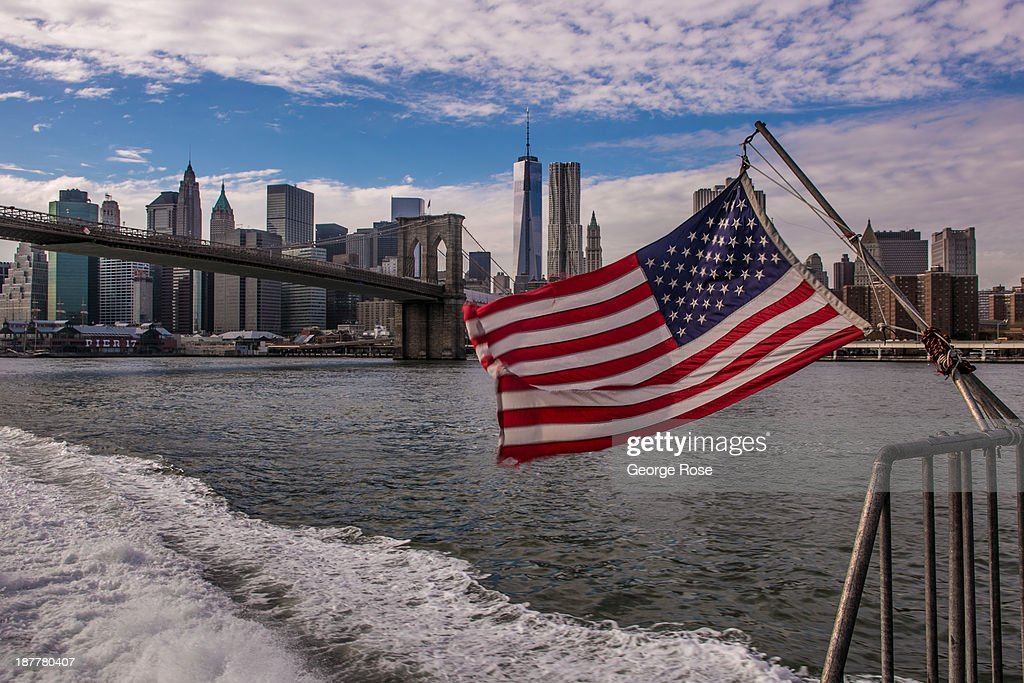 The lower Manhattan skyline is viewed while an American flag whips in the wind during a ride on the East River Ferry on October 24, 2013 in New York City. With a full schedule of conventions and major events taking place throughout Manhattan, millions of global visitors converged on New York City this fall.