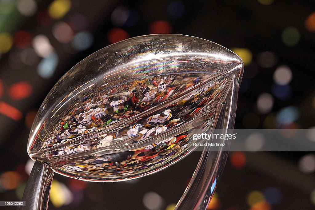 The LSU Tigers are reflected in the Cotton Bowl Championship trophy while celebrating a 41-24 win against the Texas A&M Aggies during the AT&T Cotton Bowl at Cowboys Stadium on January 7, 2011 in Arlington, Texas.
