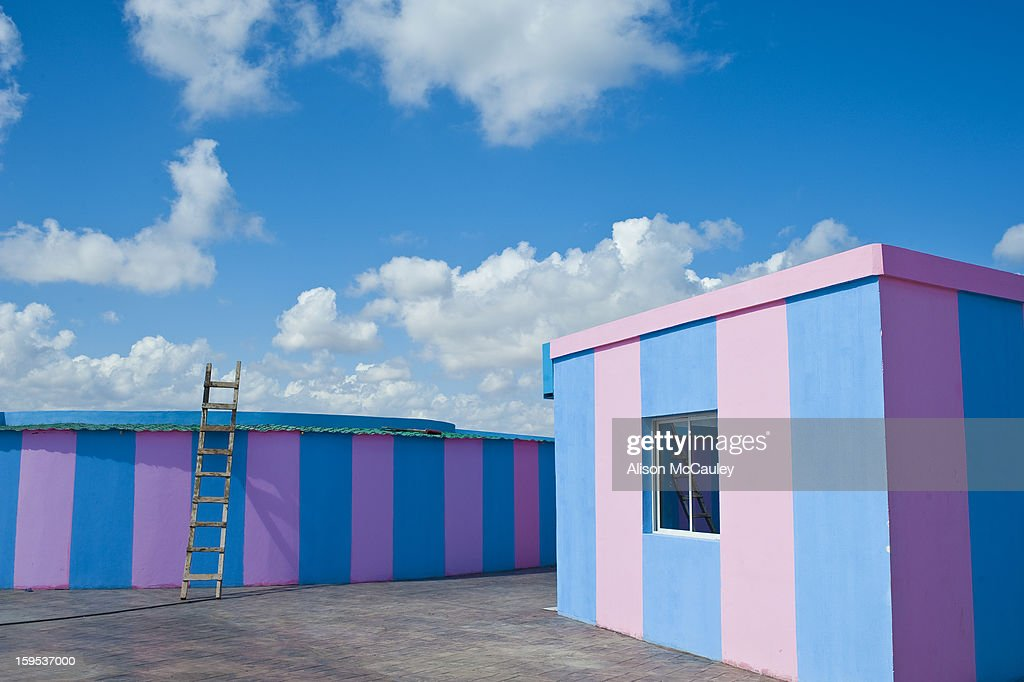 CONTENT] The ludic, bubble-gum pink and blue striped buildings seem unreal. There's no one around and a ladder that reaches straight up to to the bright blue sky with fluffy white clouds adds to the playful, slightly surreal feeling.