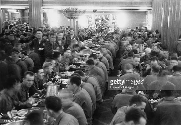 The luxury dining room of the Cunard White Star liner Queen Mary serves as a mess for American soldiers while the vessel carries out her duties as a...