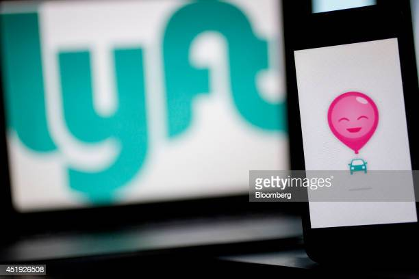 The Lyft Inc logo and application is displayed on an Apple Inc iPhone 5s and MacBook Air for an arranged photograph in Washington DC US on Wednesday...