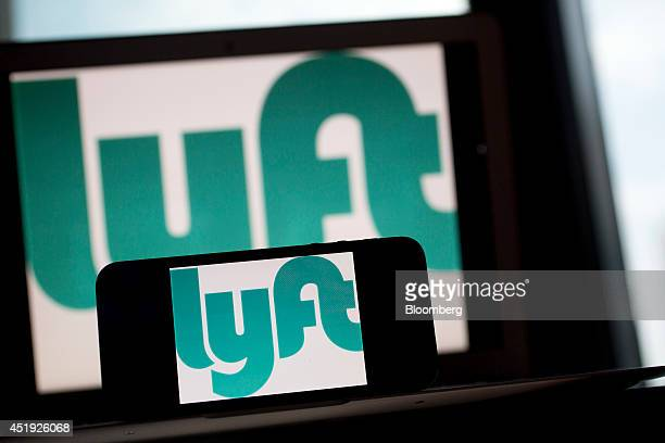 The Lyft Inc logo is displayed on an Apple Inc iPhone 5s and MacBook Air for an arranged photograph in Washington DC US on Wednesday July 9 2014 Lyft...