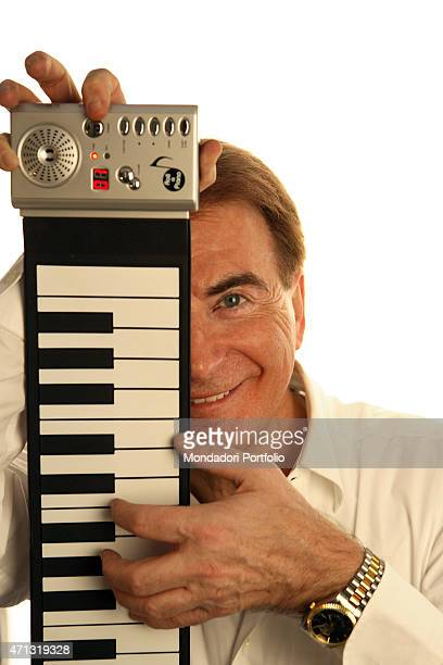 The lyricist and TV presenter Paolo Limiti playing a pianola for a photo shooting in his house in Milan Milan Italy 2007