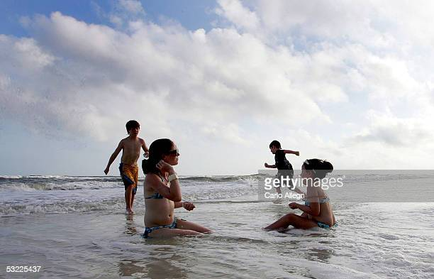 The Macguire family plays on the beach landfall July 11 2005 in Destin Florida People began returning to their communities Monday a day after...