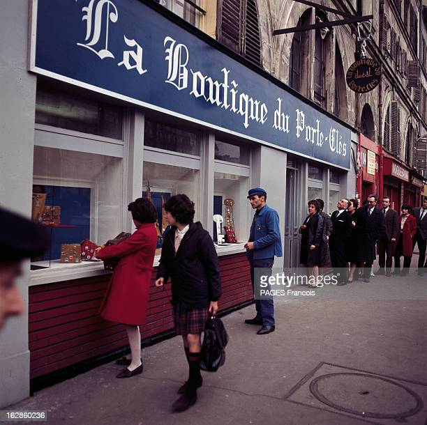 The Madness Of Keyring A Paris dans une rue des passants regardant la vitrine du magasin 'La boutique du porteclés'