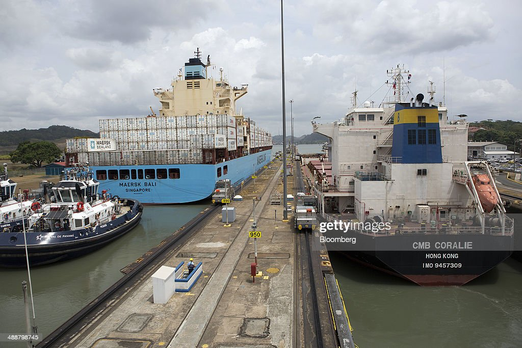 The Maersk container ship Bali, left, and the CMB Coralie bulk carrier, right, are guided through the Miraflores locks at the Panama Canal, near Panama City, Panama, on Wednesday, April, 23, 2014. Construction projects throughout Panama have remained idle since April 23, when workers walked off the job in an effort to win a 35 percent salary increase. The strike threatens to further delay the canals expansion, designed to accommodate larger ships and help reduce transport costs for commodities such as liquefied natural gas. Photographer: Susana Gonzalez/Bloomberg via Getty Images