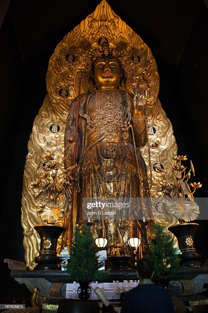 The magnificent statue of Hase Kannon at Hase-Dera Temple in Kamakura. It is 9 meters or 30 feet tall and has eleven heads in addition to its main one - three in front, three to the left and three to the right, plus one at the top and another on the back. Each face has a different expression, signifying that the deity listens to the wishes of all types of people. Gold leaf was applied to the statue in 1342 and in 1392 the halo was added. Although Kannon is usually described in English as 'the Buddhist Goddess of Mercy' strictly speaking it is neither masculine nor feminine and represents compassion, mercy, and love..