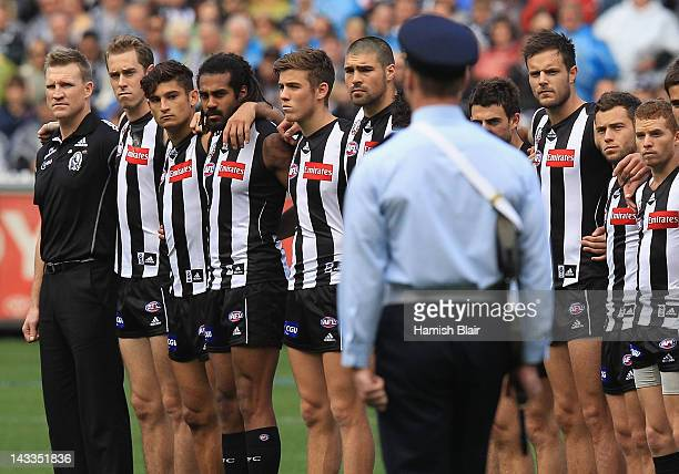 The Magpies team line up for the pre match Anzac ceremony ahead of the round five AFL match between the Collingwood Magpies and the Essendon Bombers...