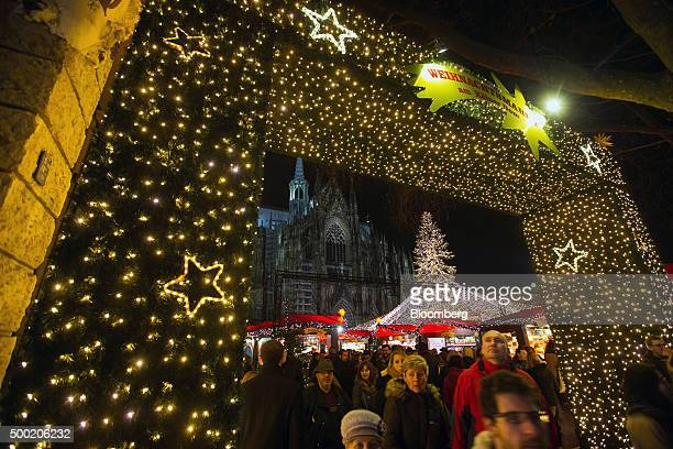 The main entrance to a Christmas market in front of the Cologne Cathedral stands illuminated as shoppers pass by in Cologne Germany on Saturday Dec 5...