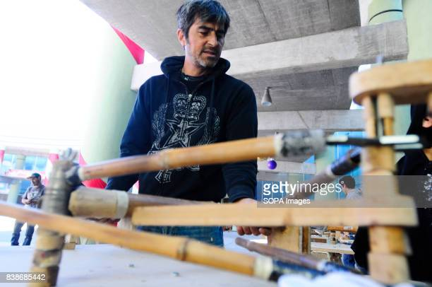 The main frame of a bamboo bicycle being manufactured People are seen during the manufacture of bicycles made with bamboo wood to promote ecological...