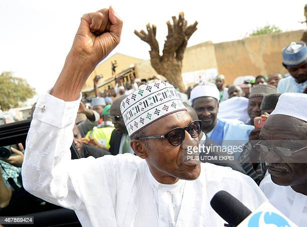 The main opposition All Progressives Congress presidential candidate Mohammadu Buhari raises fist after registering to vote on March 28 2015 in Gidan...