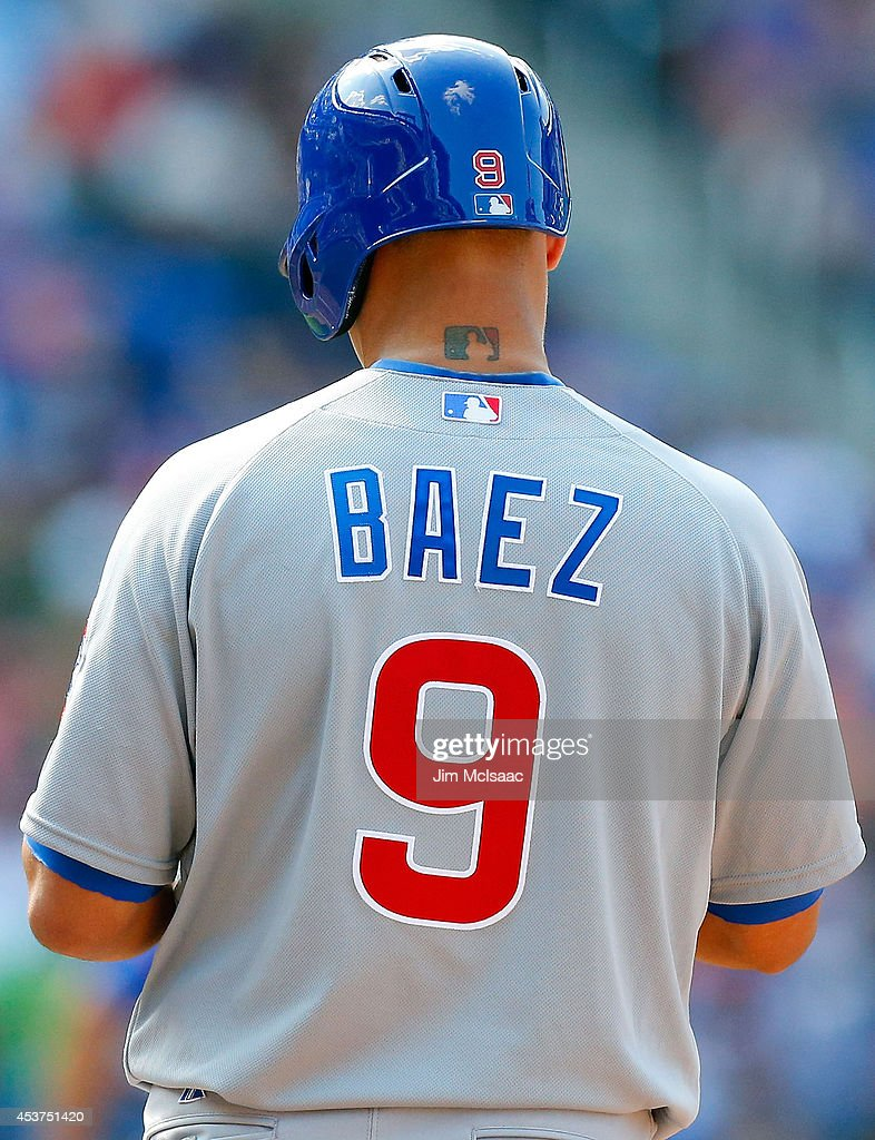 The Major League Baseball logo is seen as a tattoo on the neck of Javier Baez #9 of the Chicago Cubs as he stands on base during a game against the New York Mets at Citi Field on August 17, 2014 in the Flushing neighborhood of the Queens borough of New York City.