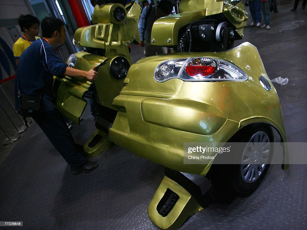 The makers check the 'feet' of the 'Transformer X2', built by Chinese cartoon fans Sui Lulu, Zhang Yiming and Li Wei, to be displayed at an exhibition center on October 8, 2007 in Nanjing of Jiangsu Province, China. The Chinese youths spent three months and over 60,000 yuan (about USD 8,000) to make the Transformer refitted from a Citroen C2 car. 'Transformer X2', standing at 4.5 meters (about 15 feet) was based on the figures of 'Bumblebee' and 'Jazz', Autobot characters in the animated series and movies.