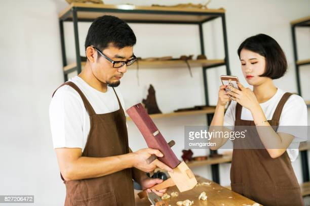 The male carpenter was instructing the young female carpenter