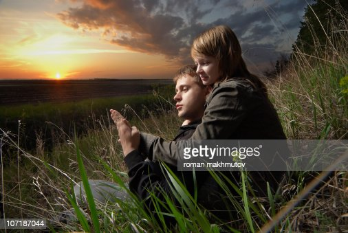 The man and a woman sitting on the sunset : Stock Photo