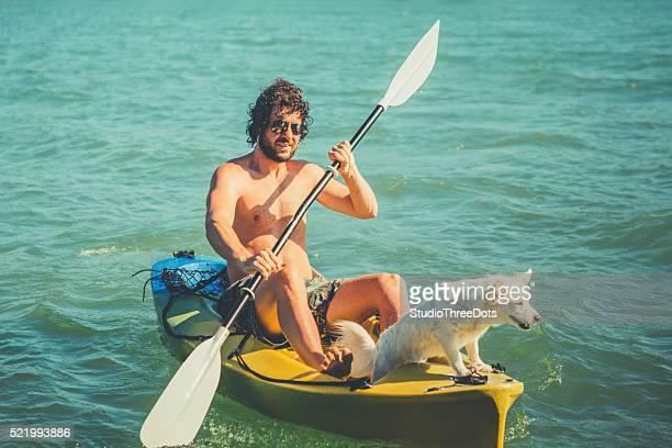 Der Mann in einem Kajak withhis Hund