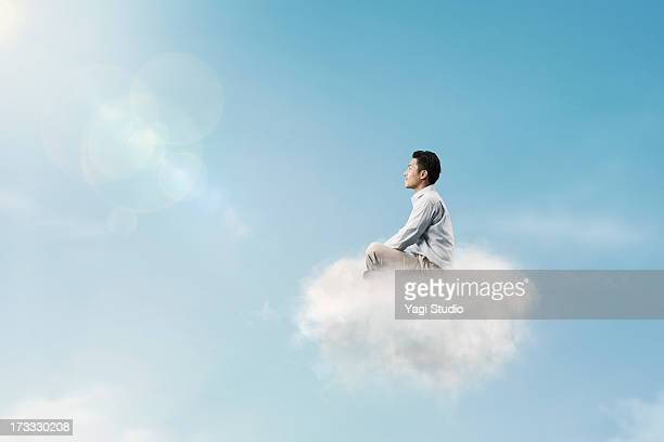 The man is relaxing above the clouds