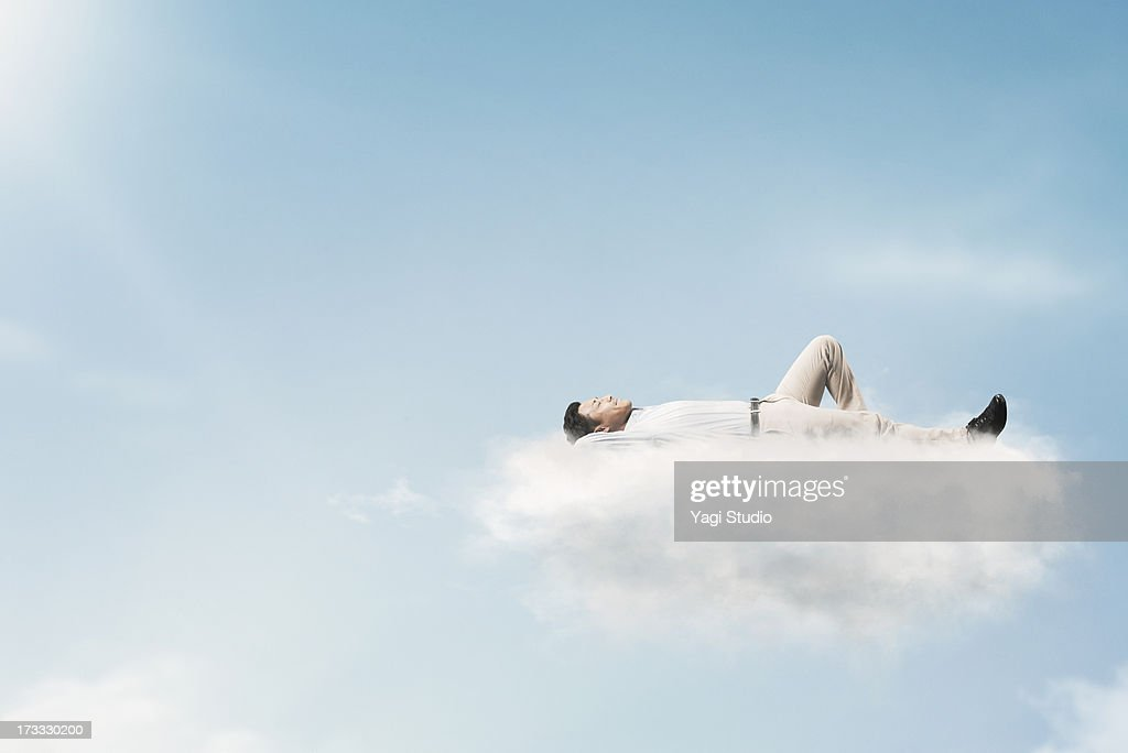 The man is relaxing in the clouds : Stock Photo