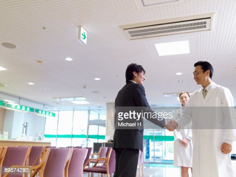 The man is shaking hands with the doctor.  : Stock Photo