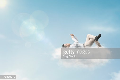 The man is using a smartphone above the clouds