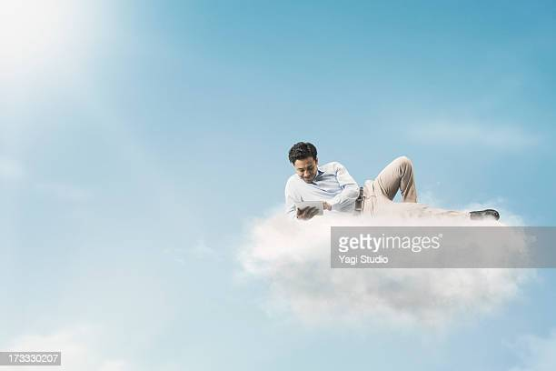 The man is using Digital Tablet above the clouds