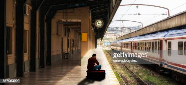 The man is waiting in railroad station platform