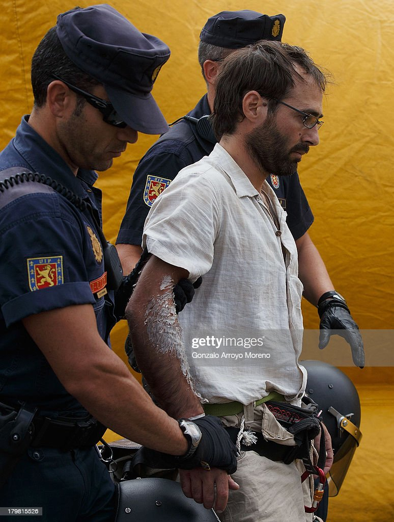 The man named 'Cobri' (2ndL) is arrested by the police after he let himself down assisted by firemen after hanging from a lampost as a protest against the Madrid 2020 Olympic Candidancy and the Madrid City Council eviction policy at Puerta del Sol on September 7, 2013 in Madrid, Spain.