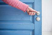 man holding a metal pen in an open wooden door blue