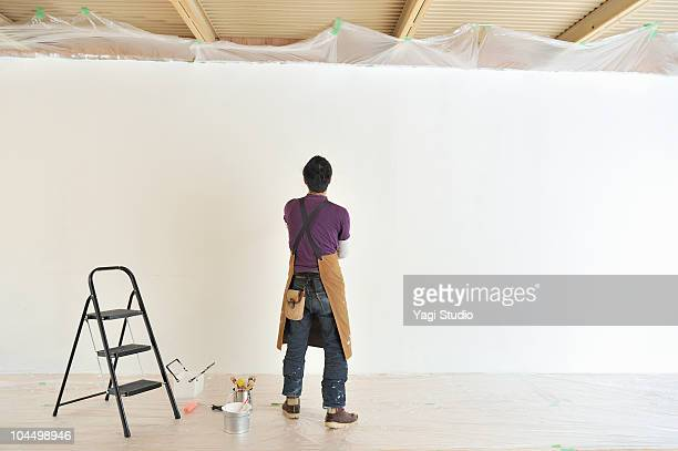 The man standing in front painted wall