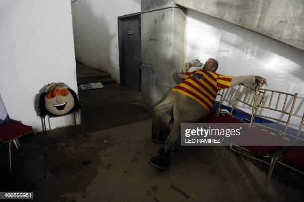 The man that works as the mascot 'Margarito' for the 2014 Caribbean baseball series rests at the backstage during the game between Dominican...