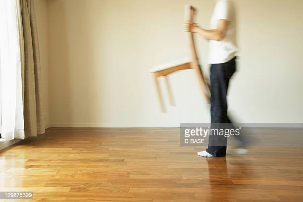 The man who carries a chair in a room