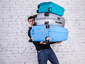 Unhappy man holding three heavy suitcases in hand. Travel light.
