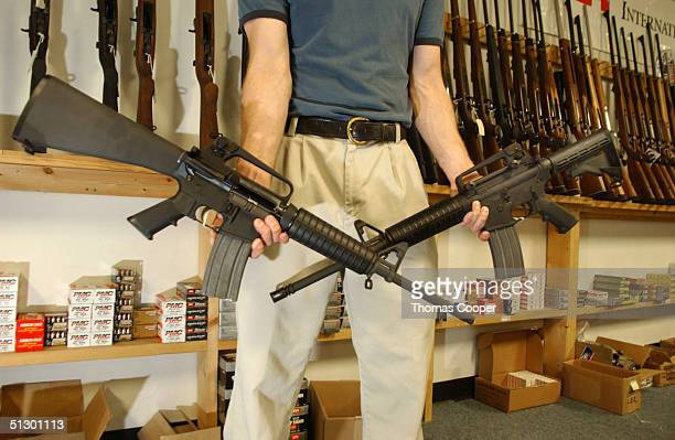 The Manager of Dave's Guns holds two Colt AR15's the gun on the right has a bayonet mount flash suppressor and a collapsible stock and accepts high...