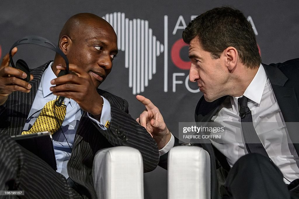 The managing director of the French business bank Lazard France, Matthieu Pigasse (R), speaks on November 21, 2012 with the chief executive officer of the Nigerian Stock Exchange, Oscar Onyema, during the 'What development strategies should African companies employ?' plenary session at the first Africa CEO Forum in Geneva. AFP PHOTO / FABRICE COFFRINI
