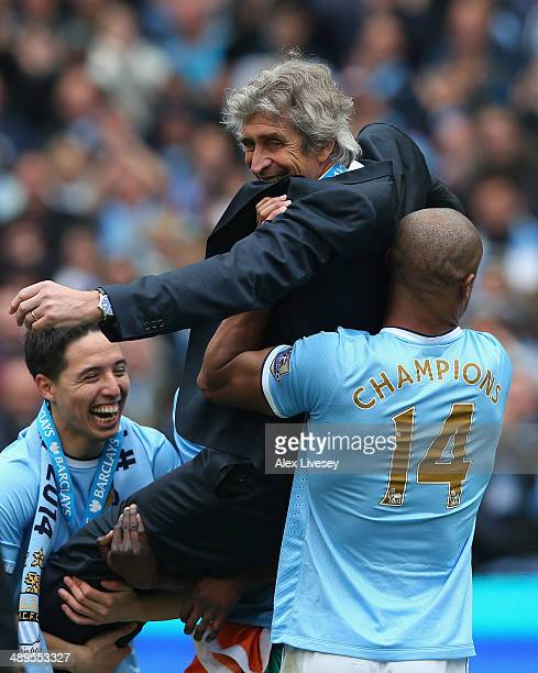 The Manchester City Manager Manuel Pellegrini is lifted up by Samir Nasri and Vincent Kompany to throw him in the air at the end of the Barclays...